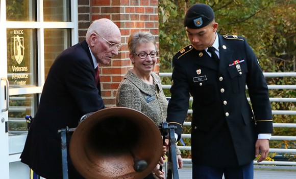 Brig. Gen. Ted Crichton, left, Chancellor Linda P. Brady and Spc. Chen-yang Liu, right, ring the university bell as they dedicate the new Veterans Resource Center.